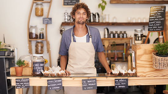 Male barista standing behind counter